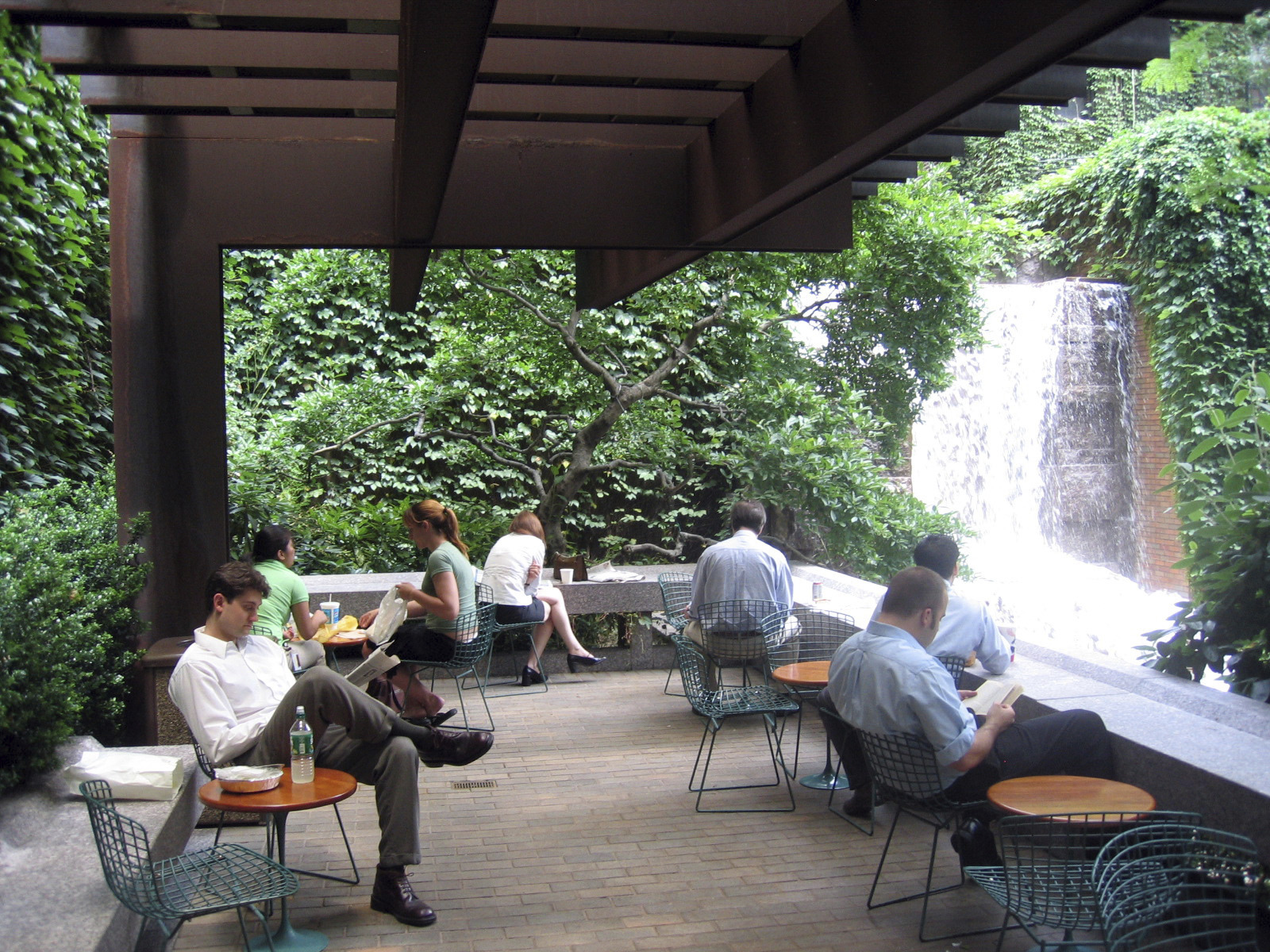 people sitting at tables near a waterfall