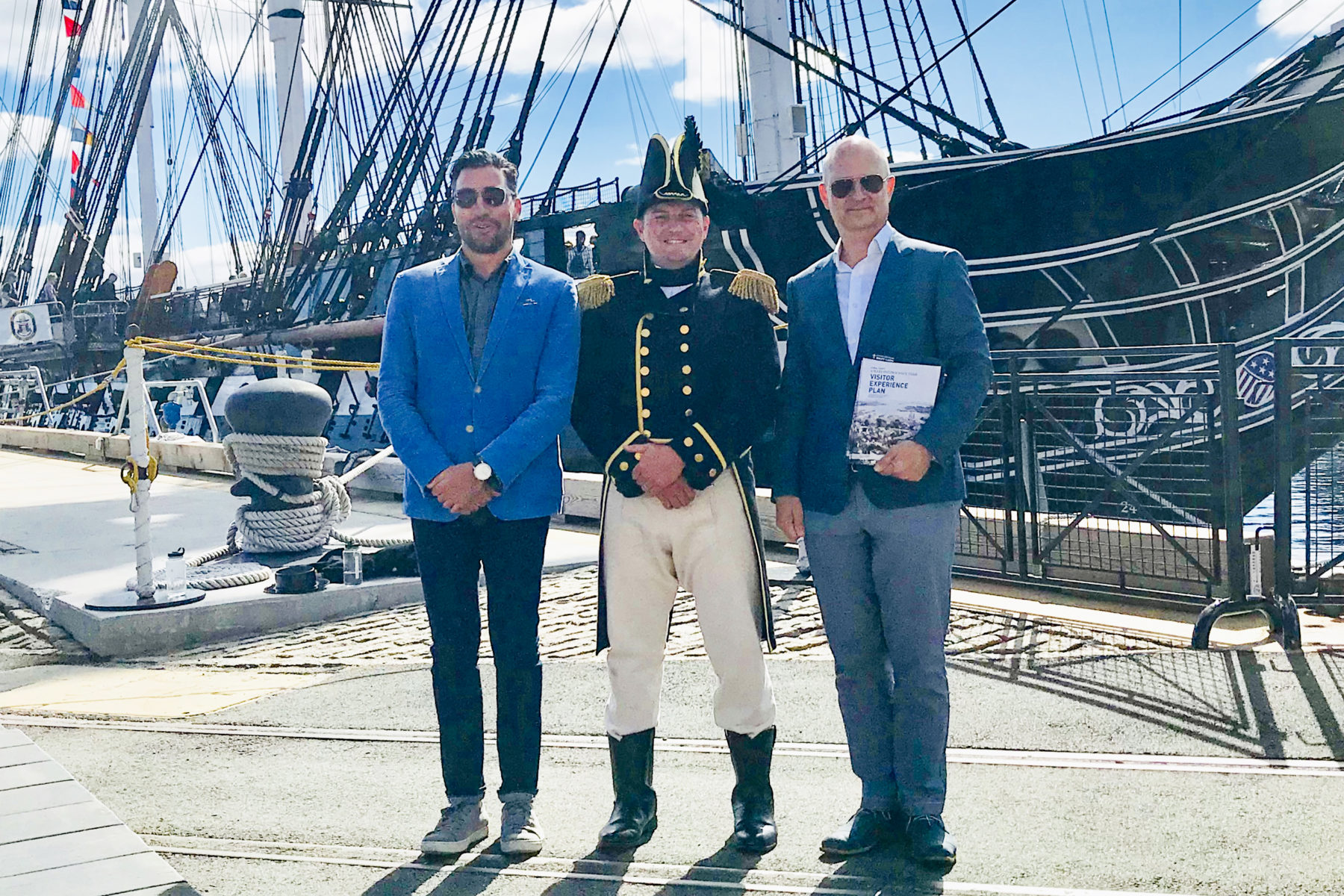 three men stand in front of a ship