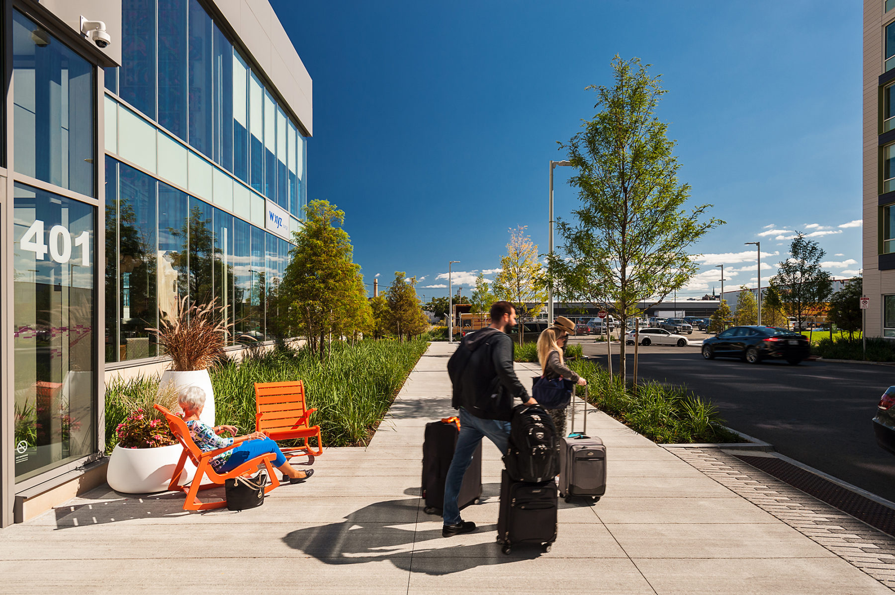 Photo of a couple exiting hotel with luggage. A woman sits in an orange chair on the sidewalk.