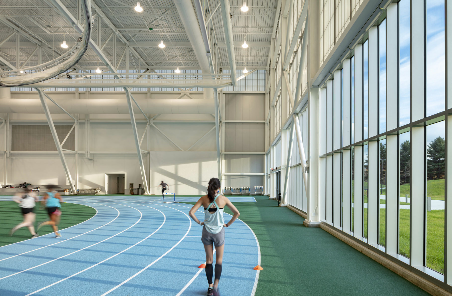interior photo of field house. Runners move along the track