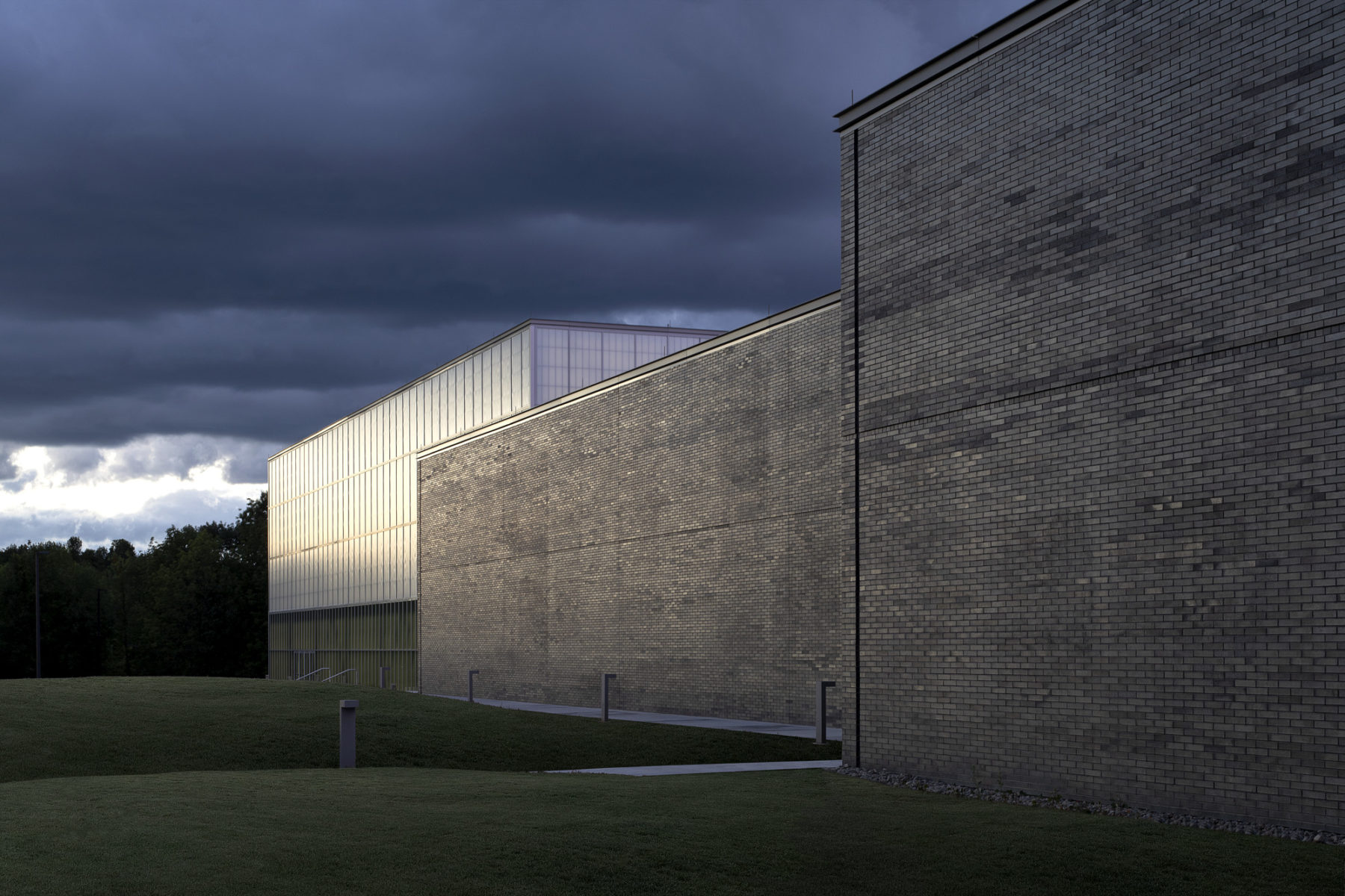 exterior photo of building - volumes of space are expressed in gray brick and curtainwall