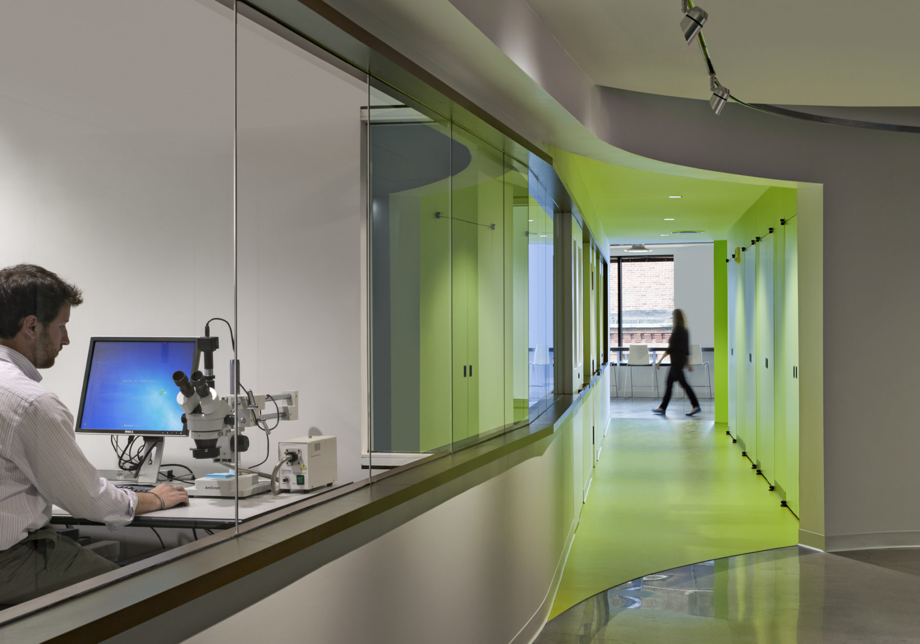 Man working on his desktop and microscope in a see-through office area towards the left, while we can look and see a greenly lit hallway on the right.