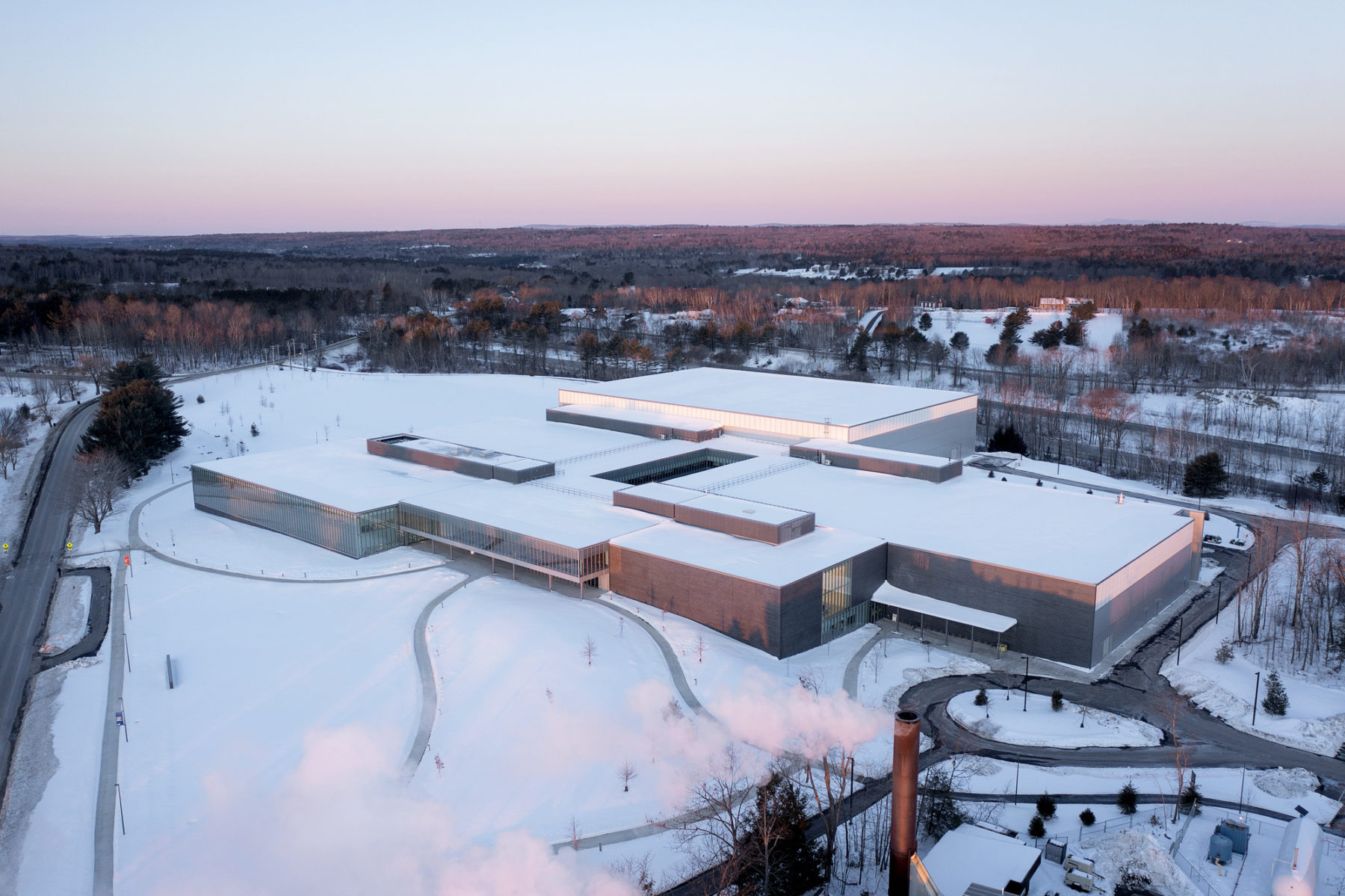 exterior aerial photo of building at dusk - landscape is snow covered