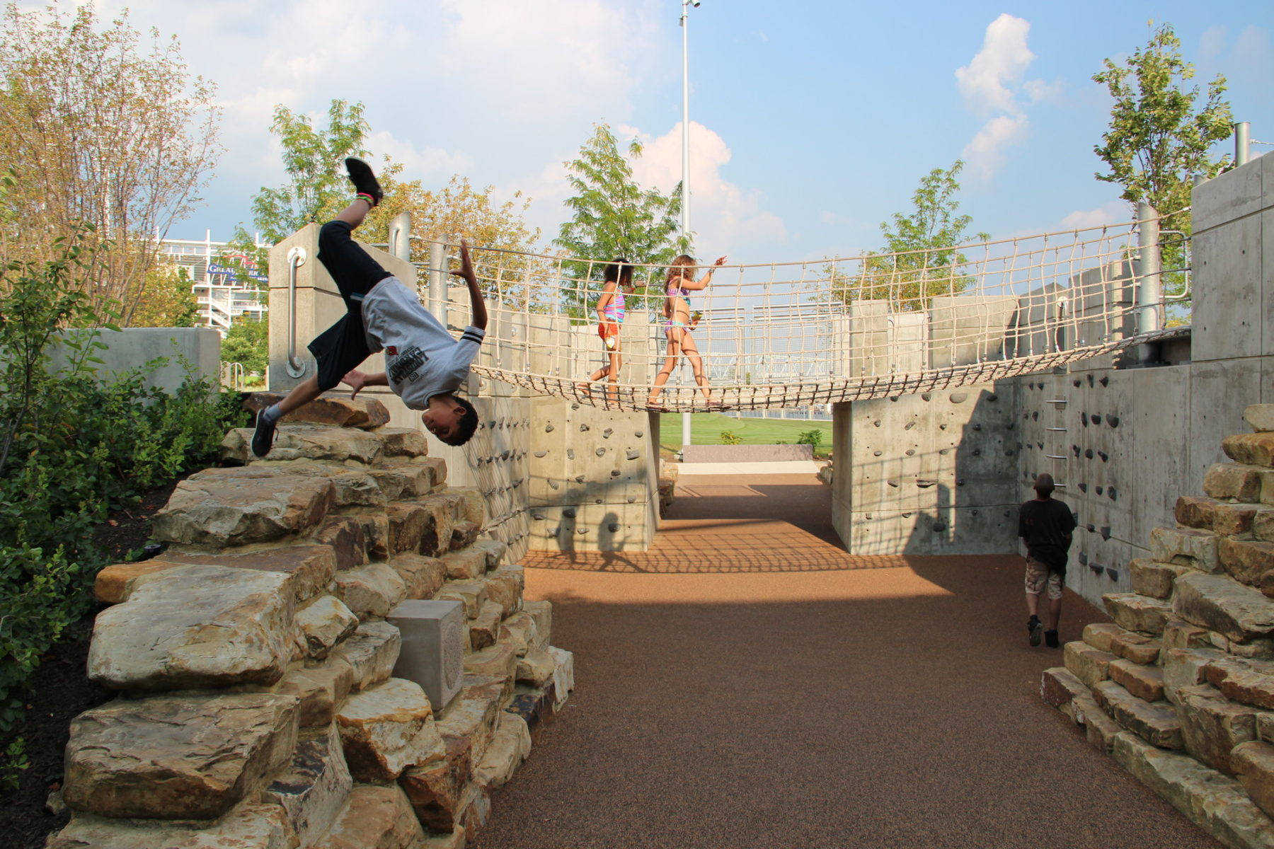 Kid doing a flip off of rock play structure