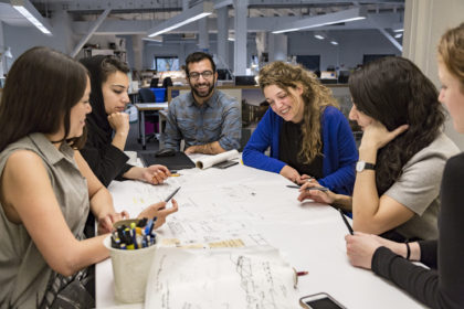 Photo of group gathered around a table discussing the design idea over a drawing
