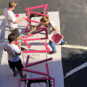 People painting pieces of a chicken coop pink, seen from above