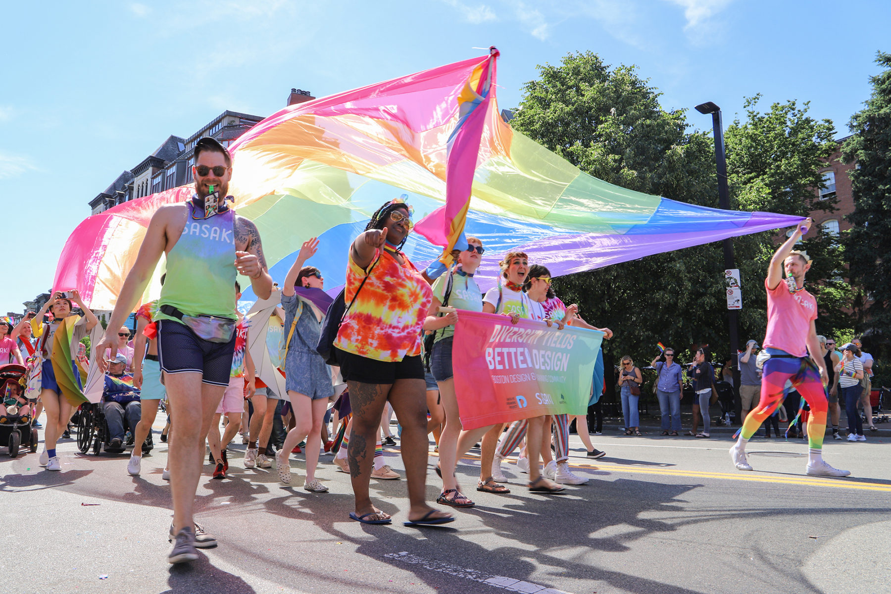 Sasakians marching in Boston's 2019 Pride Parade holding a flag overhead