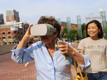 a woman views a 3D panoramic image through a headset