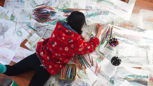 A person lying on the ground drawing, surrounded by drawings and colored pencils
