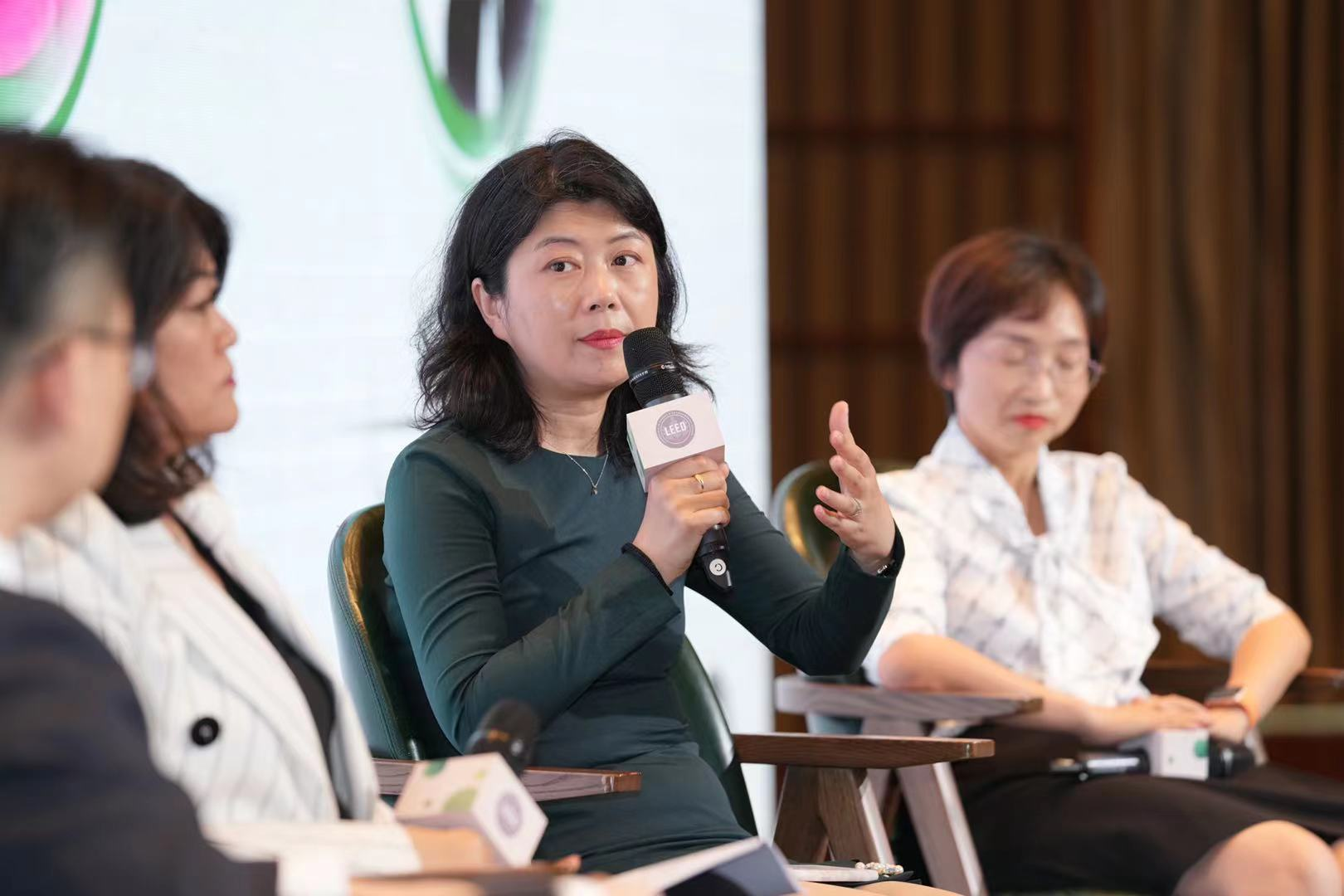 Dou Zhang sits on stage with three other panelists and a microphone in her hand, speaking