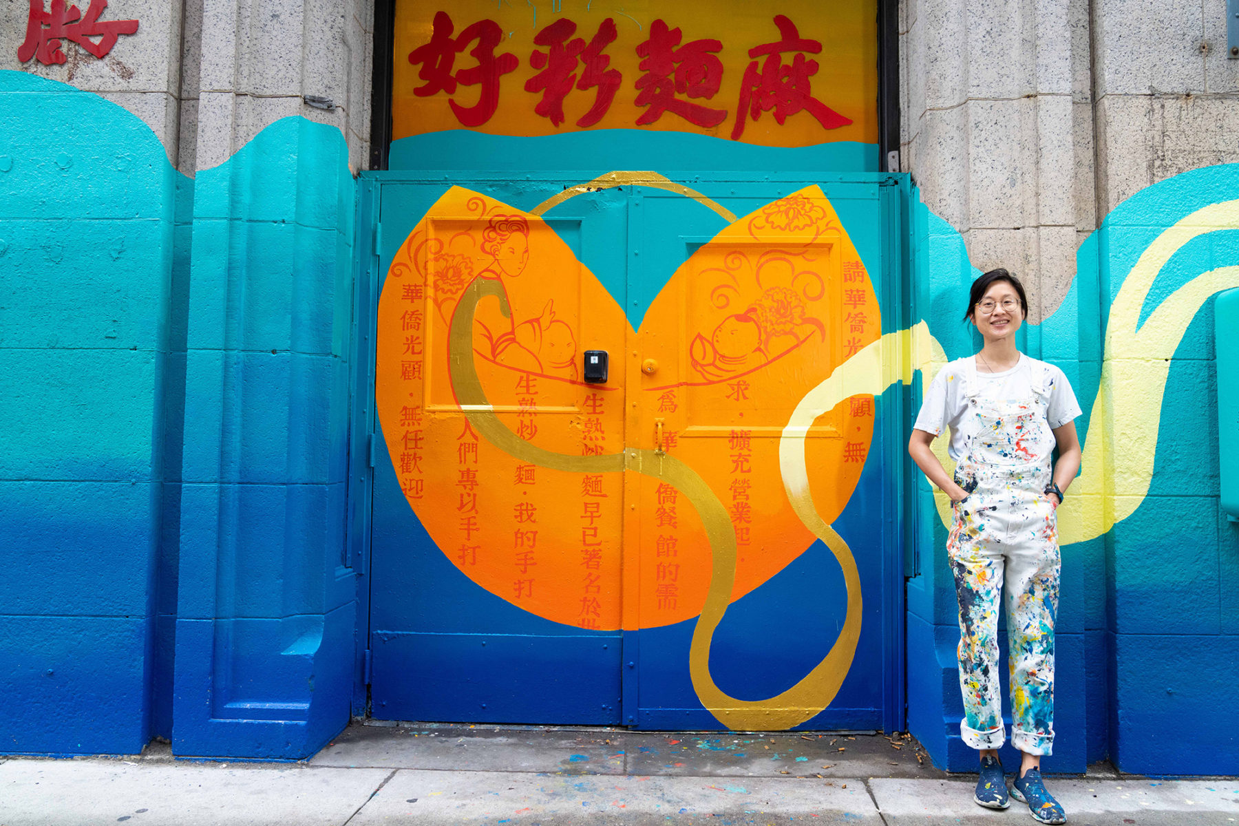 Artist stands by vibrant colored mural painted over doors