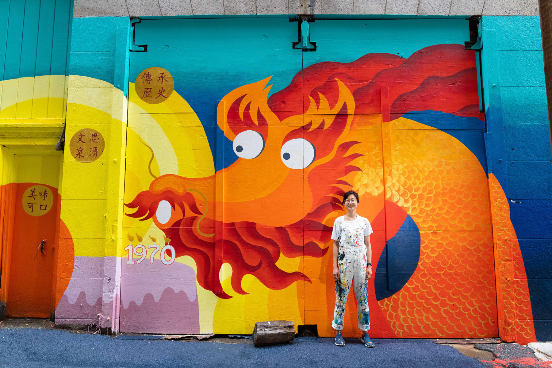 Artist stands in front of brightly colored mural in Chinatown